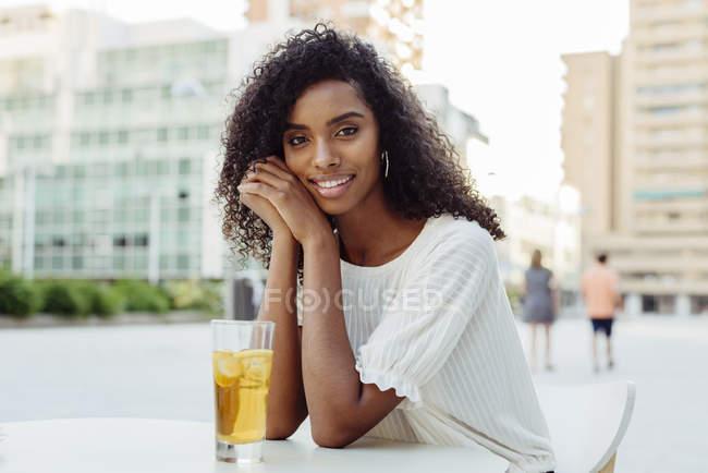 Mulher afro-americana encantadora sentada com um copo de bebida no café ao ar livre — Fotografia de Stock