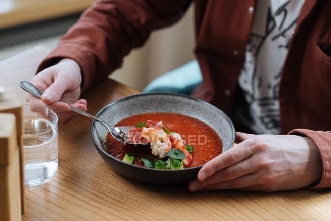 Hombre comiendo sopa roja nórdica tradicional adornada con hierbas - foto de stock