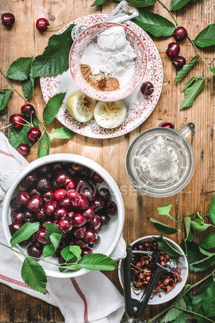 Flat lay of ceramic bowl filled with cherries and composed with green leaves, sugar and lemon on rustic table — Stock Photo