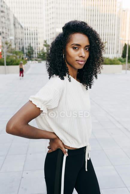 Riendo mujer afroamericana de pie en la calle y mirando a la cámara - foto de stock