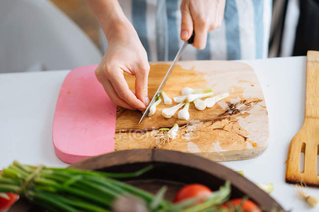 Female Cutting Spring Onion With Knife On Chopping Board In