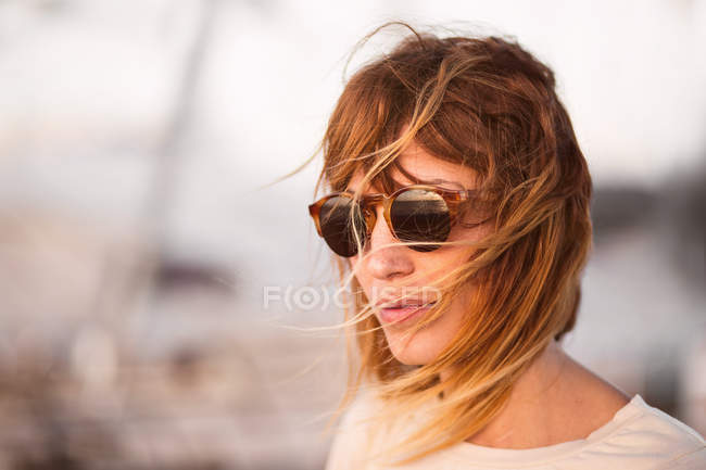 Woman with flying blond hair in modern sunglasses looking away outside — Stock Photo