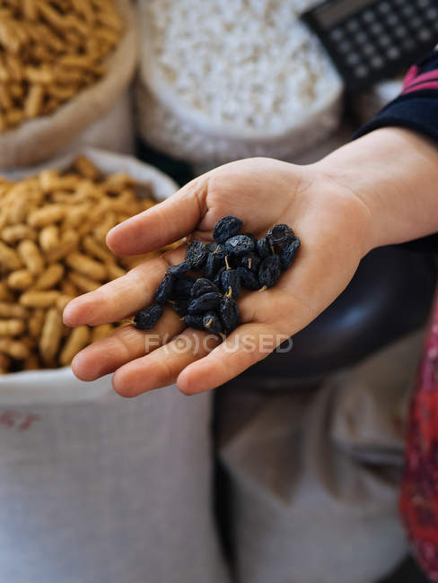 Fabric bags of dry fruits and hand with raisins — Stock Photo