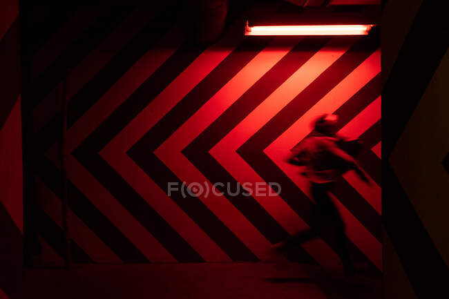Side view of motion blurred figure of male walking down in tunnel in direction opposite to large red and black arrows on wall lit by red lamps — Stock Photo