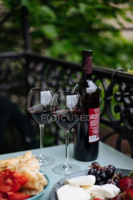 Bouteille de vin et verres délicats avec de hautes tiges debout sur la table avec des tomates tranchées, du pain, du fromage et des baies allongées sur des assiettes avec une clôture ornementale et des plantes sur le fond — Photo de stock