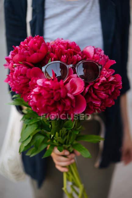 Крупным планом женщина держит букет розовых пионов с очками на вершине — стоковое фото