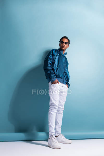 Portrait of black man in blue bomber jacket and sunglasses standing on blue background — Stock Photo