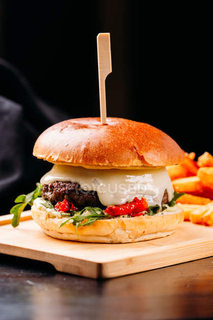 Close-up of fresh burger with meat patty and vegetables placed on wooden board with French fries on wooden board — Stock Photo