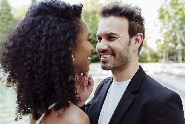 Charmantes gemischtrassige paar umarmt und sahen einander im freien — Stockfoto