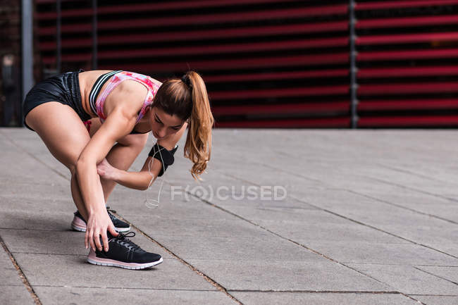 Flexible woman stretching body on street — Stock Photo