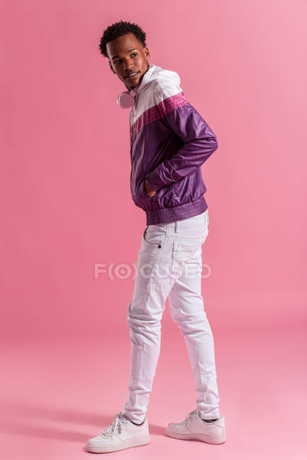 Stylish hipster man in colorful jacket with headphones standing on pink background — Stock Photo