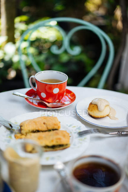 Red ceramic polka-dotted mug on saucer and pieces of pasty on plate on garden table — Stock Photo