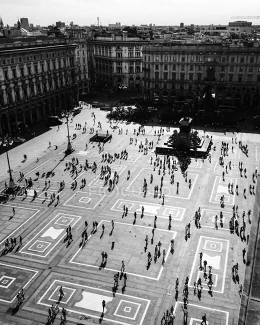 Fotografia aérea em preto-e-branco da antiga praça ornamentada com monumento no centro e pessoas andando cercadas por belos edifícios antigos de vários andares no dia ensolarado — Fotografia de Stock