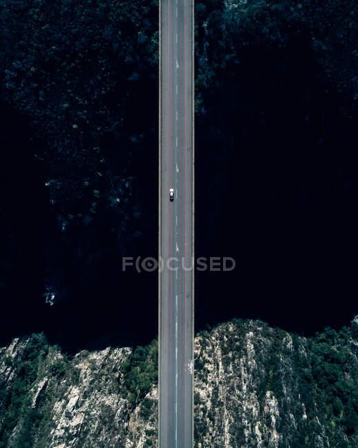 Вид с воздуха на небольшую машину, движущуюся по пустой дороге моста через залив Темного океана с каменистой береговой линией — стоковое фото