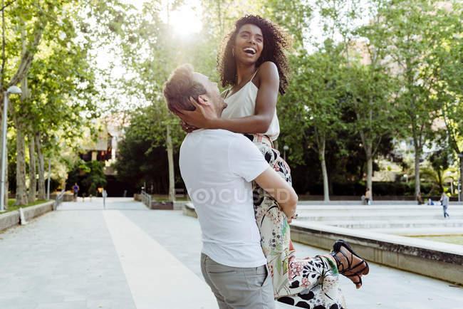 Mann hebt lachende Frau an sonnigem Tag in Parkgasse an — Stockfoto
