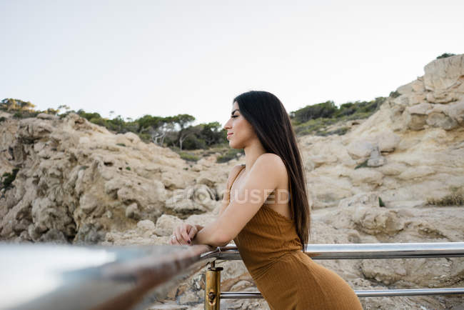 Side view of stylish woman leaning on fence against coastline — Stock Photo