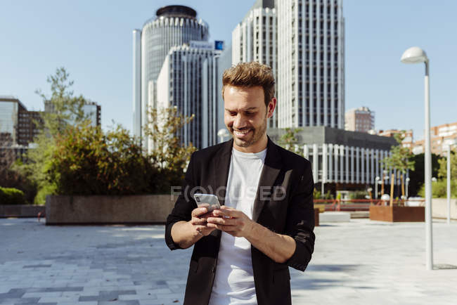 Élégant sourire gars navigation smartphone sur la rue de la ville moderne — Photo de stock