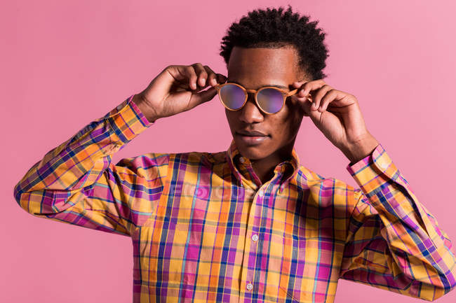Trendy black man wearing colorful checkered shirt with shiny pink sunglasses standing on pink background — Stock Photo