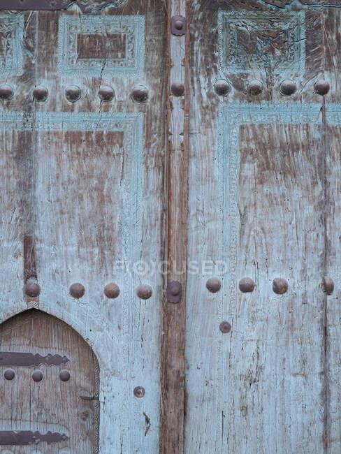Крупный план текстуры старой двери с выветриваемой деревянной поверхностью в металлических ржавых заклепках, Узбекистан — стоковое фото