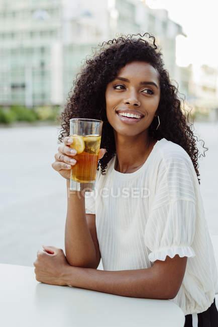 Charmante femme afro-américaine, tenant le verre de boisson au café en plein air — Photo de stock