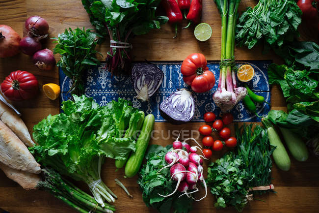 Fresh vegetables and greens on wooden table — Stock Photo