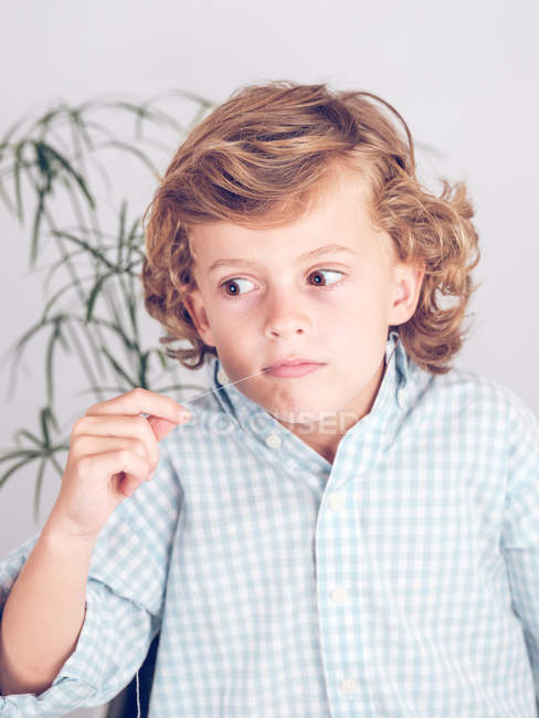 Adorable boy making scared grimace and pulling tooth out with thread — Stock Photo