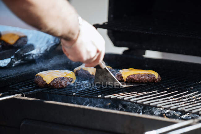 Crop shot of man roasting meat patties with cheese on smoking grill in sunlight — Stock Photo