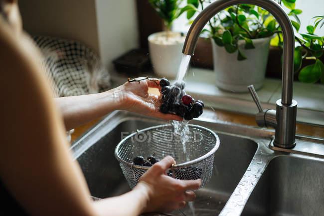 Человеческие руки мытья винограда под раковиной кран на кухне — стоковое фото