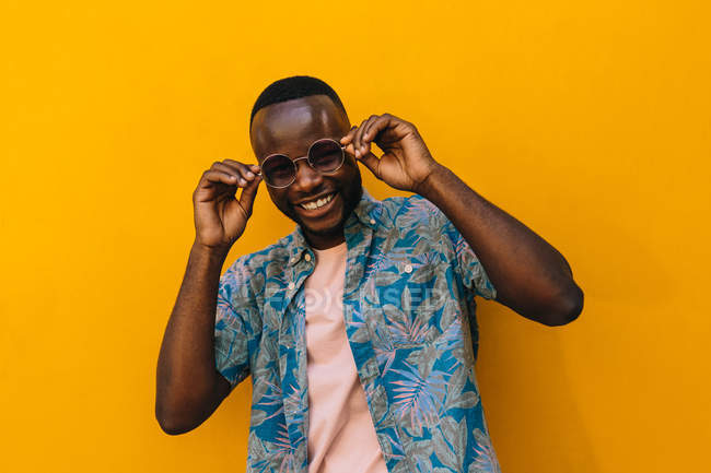 Handsome African American man in sunglasses smiling against bright yellow background — Stock Photo