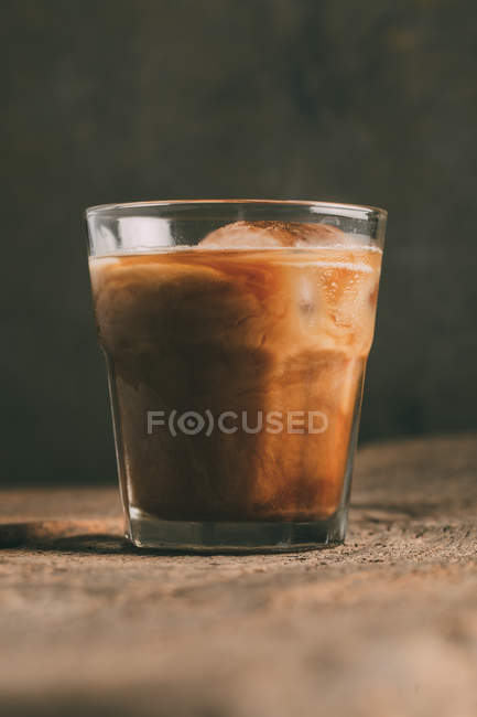 Ice cold brew coffee in glass on wooden surface — Stock Photo