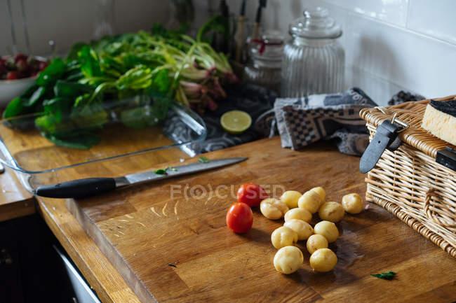 Frische Tomaten gewaschen und geschält Kartoffeln auf Schneidbrett aus Holz mit Messer in der Küche — Stockfoto