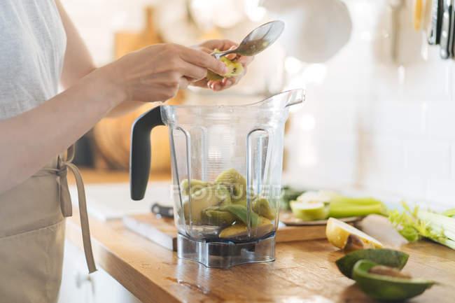 Mani femminili mettendo frutta in ciotola frullatore per frullato verde — Foto stock