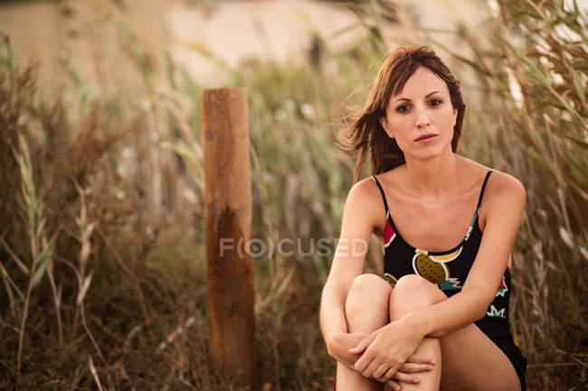 Femme en tenue d'été assis dans l'herbe haute et regardant la caméra — Photo de stock