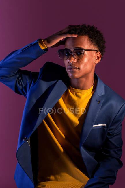 Schönen jungen afrikanischen amerikanischen Mann in Pullover und Jacke mit der Hand auf das Haar Blick in die Kamera im Lampenlicht — Stockfoto