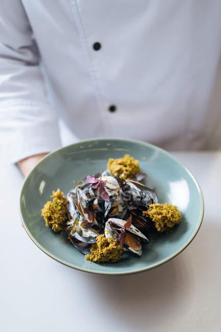 Шеф-повар Холдинг блюдо северных из морепродуктов с мидиями и сливочным соусом на плите — стоковое фото