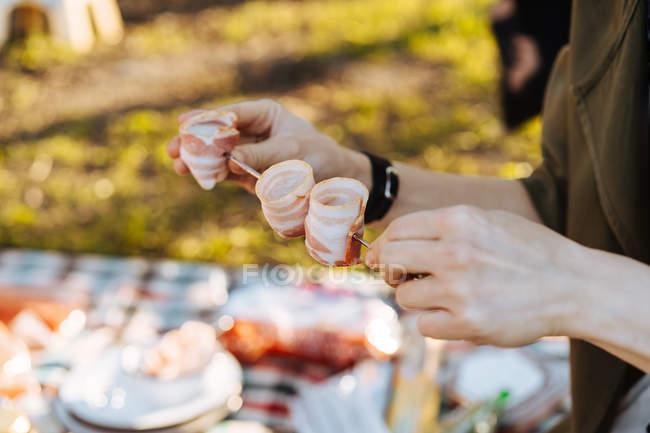 Человеческие руки укладывают сложенные полоски бекона на металлический шампур для барбекю — стоковое фото