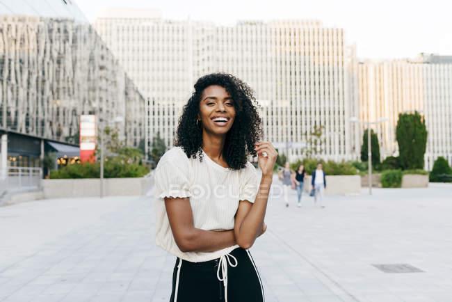 Смеющаяся афроамериканка, стоящая на улице и смотрящая в камеру — стоковое фото