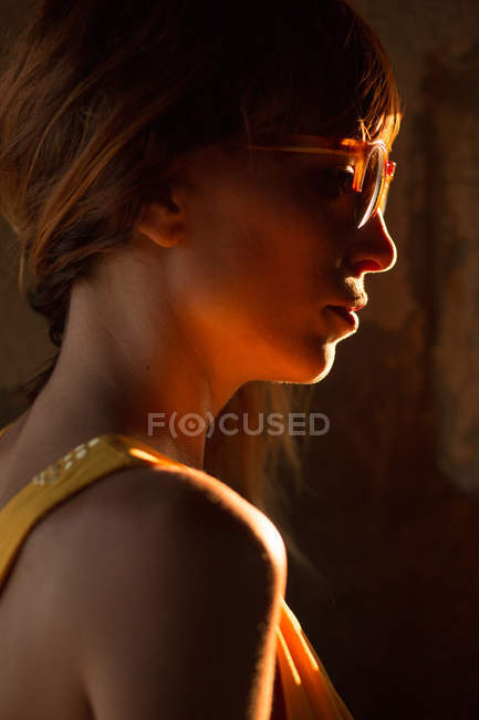 Femme portant des lunettes de soleil dans l'illumination de la lumière du coucher du soleil à la recherche de suite — Photo de stock