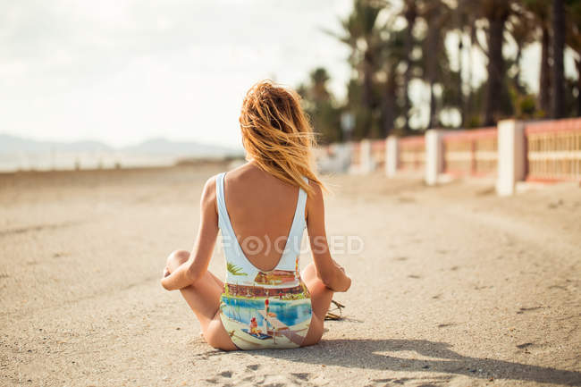 Back view of slim woman in colorful swimsuit sitting on sand and looking away — Stock Photo