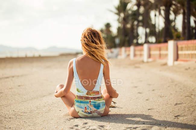 Vista traseira da mulher magro em maiô colorido sentado na areia e olhando para longe — Fotografia de Stock