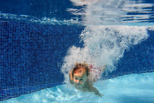 Child swimming in blue pool underwater with air bubbles — Stock Photo