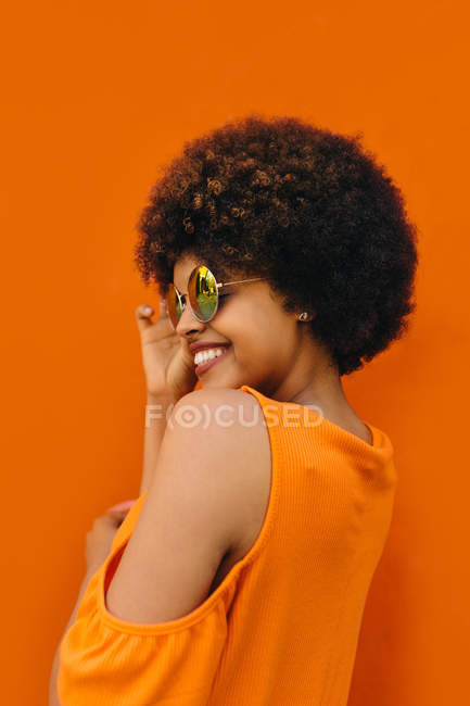 Side view of lovely black woman charmingly smiling and adjusting stylish sunglasses against orange background — Stock Photo