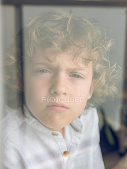 Vista de cerca de un lindo niño rubio con el pelo rizado en camisa blanca llorando silenciosamente con los labios fruncidos mirando a la cámara hecha a través del vidrio de la ventana - foto de stock