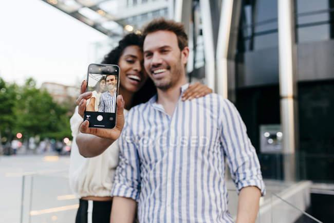 Heureux couple posant pour selfie lorsque vous êtes debout sur fond de ville moderne — Photo de stock
