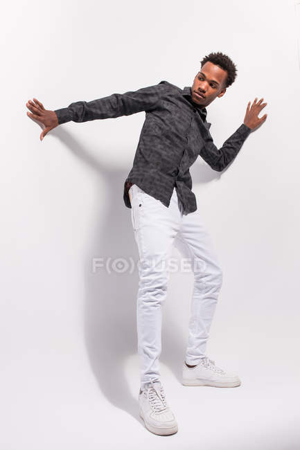 Jovem afro-americano na moda em ganga branca e camisa de pé sobre fundo branco na postura — Fotografia de Stock