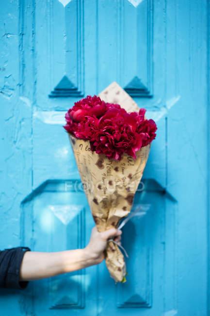 Main tenant un bouquet vif de pivoines roses en papier d'emballage devant la porte bleue en bois — Photo de stock