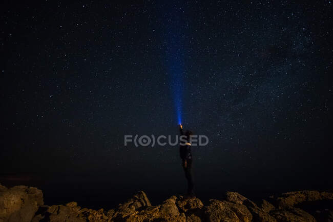 Man lighting the Man shining a flashlight to the stars at night at night — Stock Photo