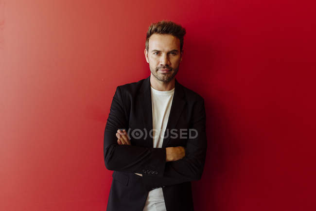 Portrait of serious man in elegant outfit standing on bright red background — Stock Photo