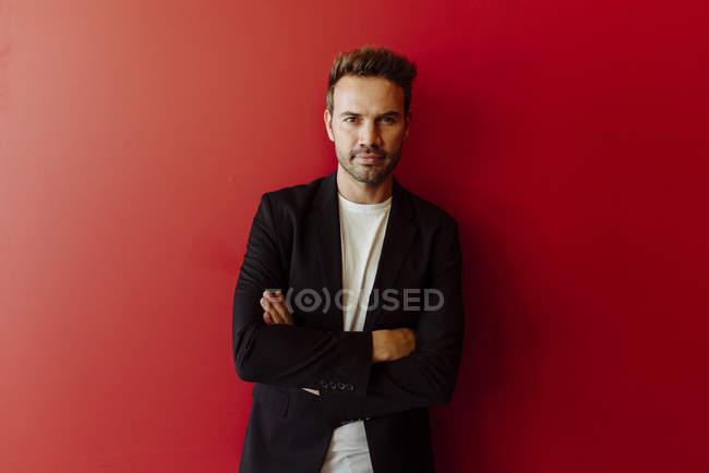Retrato de homem sério em roupa elegante em pé sobre fundo vermelho brilhante — Fotografia de Stock