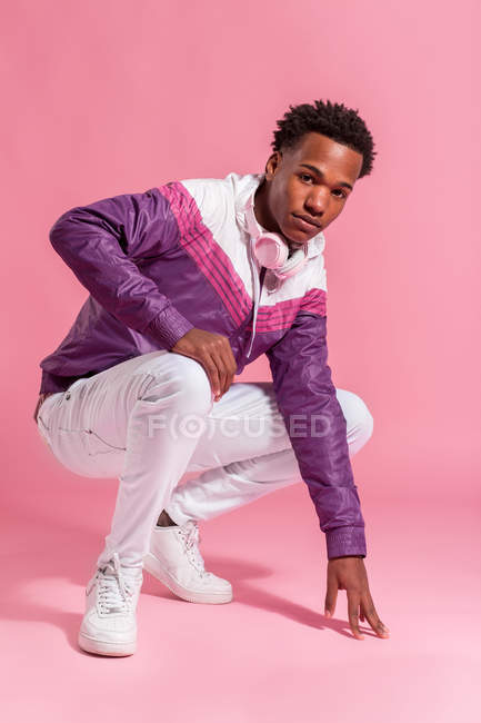 Stylish hipster man in colorful jacket with headphones on pink background — Stock Photo